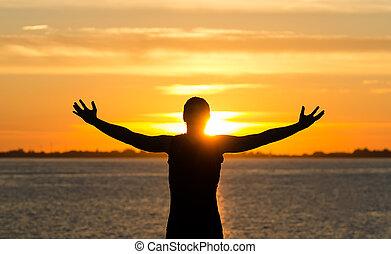Ein Mann mit weit geöffneten Armen am Strand bei Sonnenaufgang
