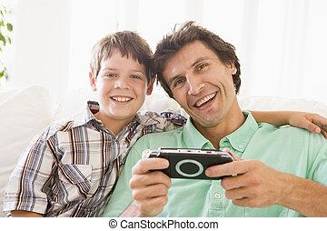Ein Mann und ein junger Junge mit einem Handspiel lächelnd