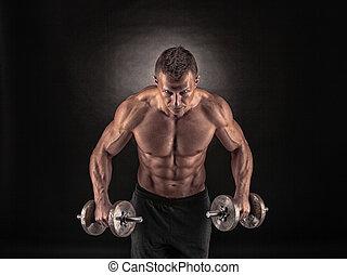 Ein muskulöser Mann mit Dumbells im schwarzen Hintergrund