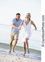 Ein Paar am Strand, das spielt und lächelt