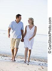 Ein Paar am Strand hält Händchen und lächelt