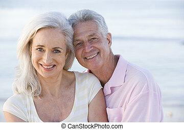 Ein Paar am Strand lächelt