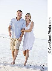 Ein Paar am Strand mit Händen und Lächeln.