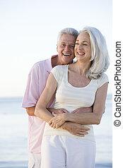 Ein Paar am Strand umarmt und lächelt
