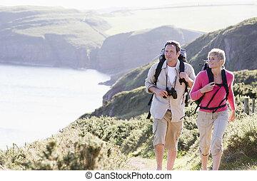 Ein Paar auf den Klippen im Freien spazieren und lächelnd