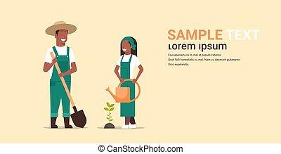 Ein paar Bauern, die Baum-Mann mit Schaufel Frau mit Wasser halten kann afrikanische amerikanische Gärtner arbeiten in der Garten-Garten-Konzept Volllänge Kopie Raum horizontal.