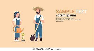 Ein paar Bauern, die junge Baum-Mann mit Schaufel Frau mit Wasser-Körper-Gärten Gärtnern arbeiten im Garten-Garten-Konzept Wohnung Volllänge Kopie Raum horizontal.