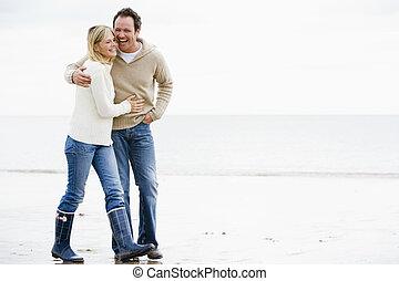 Ein Paar, das lächelnd am Arm am Strand spazieren geht