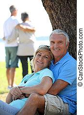 Ein Paar, das sich auf den Baumstamm lehnt