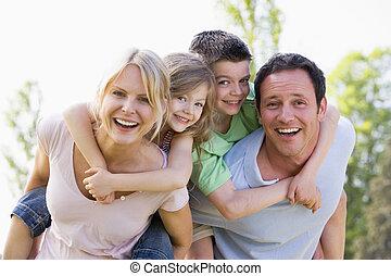 Ein Paar, das zwei junge Kinder zum Huckepack bringt und lächelt