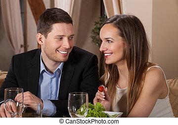 Ein paar lachen in einem Restaurant.