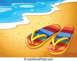 Ein Paar Sandalen am Strand.