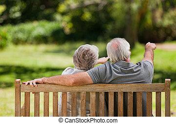 Ein Paar sitzt auf der Bank mit dem Rücken zur Kamera
