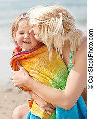 Ein Porträt einer Mutter, die ihre lachende Tochter küsst
