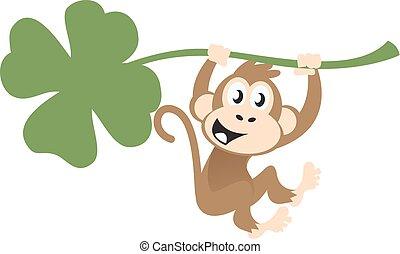 Ein süßer Affe hängt an einem Klee.