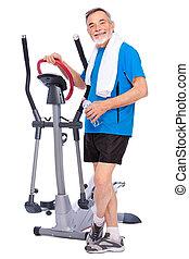 Ein Senior, der auf Stepper trainiert