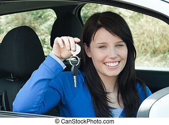 Ein strahlender Teenager mit Autoschlüsseln in ihrem neuen Auto