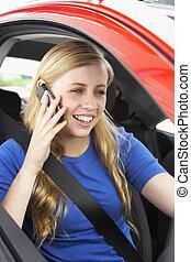 Ein Teenager, der im Auto sitzt und am Handy redet