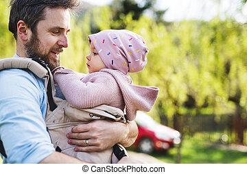 Ein Vater mit seiner Kleinkindtochter in einem Babyträger draußen auf einem Frühlingsspaziergang.