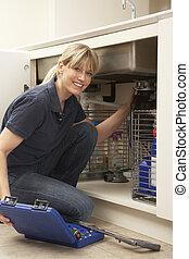 Ein weiblicher Klempner arbeitet an der Spüle in der Küche