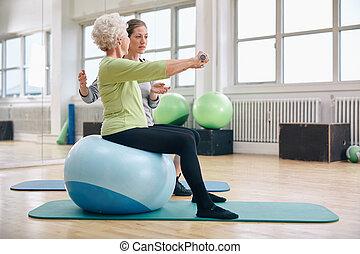 Ein weiblicher Trainer, der Senioren bei der Gewichtung unterstützt