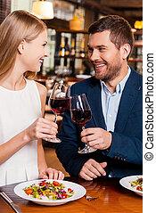 Ein wunderschönes, junges, liebevolles Paar, das mit Rotwein und Lächeln im Restaurant geröstet ist.