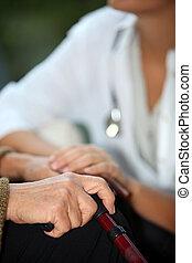 Eine ältere Frau, die mit einer Krankenschwester spricht