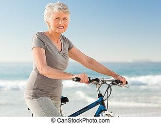 Eine ältere Frau mit ihrem Fahrrad