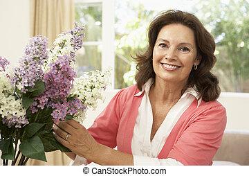 Eine ältere Frau zu Hause, die Blumen sortiert