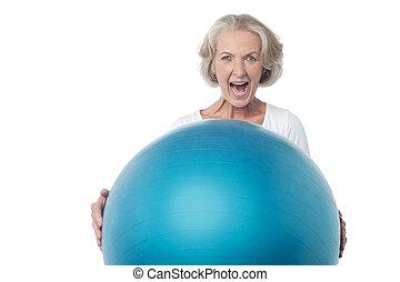 Eine alte Frau, die mit Sportball posiert.