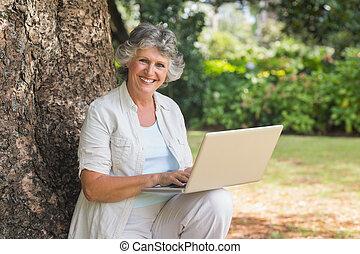 Eine erwachsene Frau, die einen Laptop benutzt, der auf dem Baumstamm sitzt