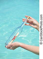 Eine Flasche mit einer Nachricht in den Händen