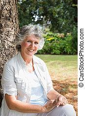 Eine fröhliche reife Frau, die auf dem Baumstamm sitzt