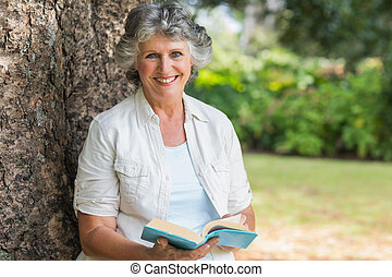 Eine fröhliche reife Frau, die Buch auf dem Baumstamm hält