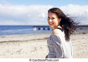 Eine Frau, die am Strand spazieren geht