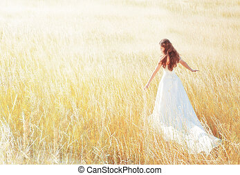 Eine Frau, die auf der sonnigen Wiese am Sommertag Gras berührt