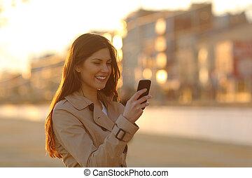 Eine Frau, die bei Sonnenuntergang ein Smartphone benutzt.