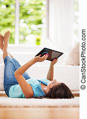 Eine Frau, die digitale Tafel zu Hause benutzt