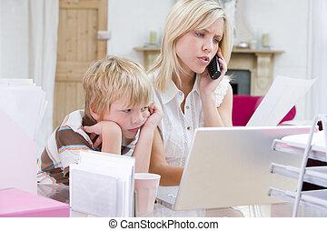 Eine Frau, die im Büro mit Laptop telefoniert, während der Junge