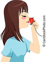 Eine Frau, die Rose riecht.