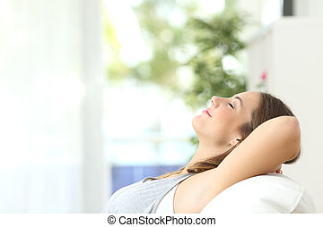 Eine Frau, die sich zu Hause auf einer Couch entspannt.