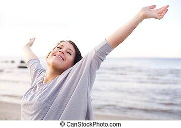 Eine Frau genießt die frische Luft des Meeres