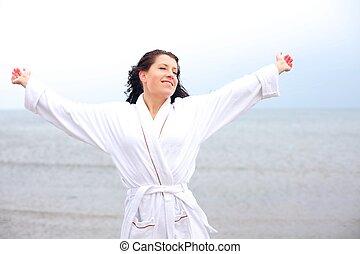 Eine Frau genießt die kühle frische Luft am Strand