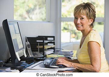 Eine Frau im Büro, die Computer lächelt