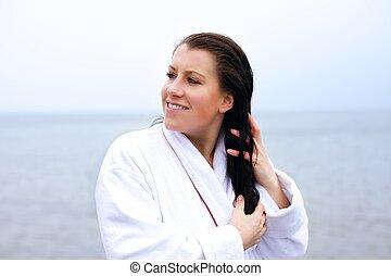 Eine Frau im Bademantel, die ihre Haare hält