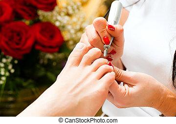 Eine Frau im Nagelstudio bekommt Pediküre.