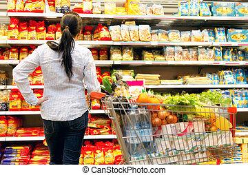 Eine Frau im Supermarkt mit einer großen Auswahl
