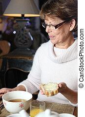 Eine Frau isst Frühstück