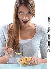 Eine Frau isst Frühstücksflocken