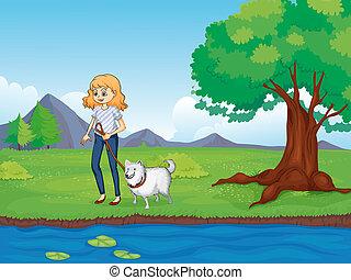 Eine Frau mit einem Hund, die am Fluss entlangläuft